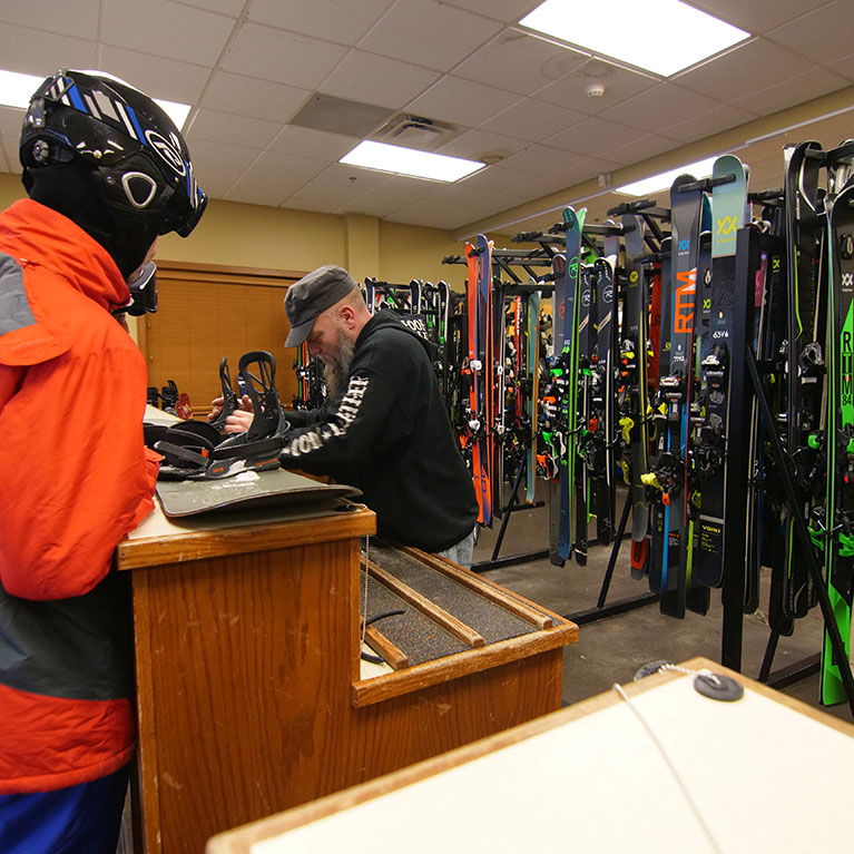 Man checking snowboard at the ski rental counter