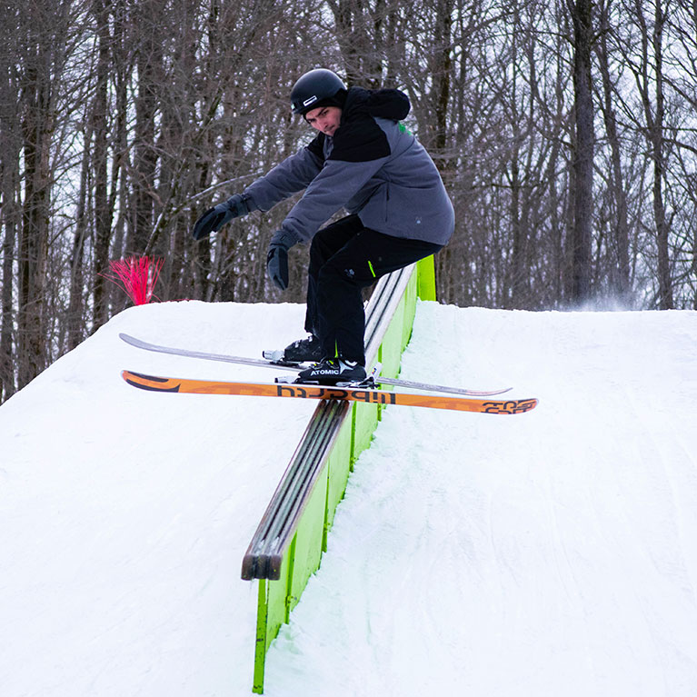 Skier riding sideways down rail in the ski and snowboard terrain park