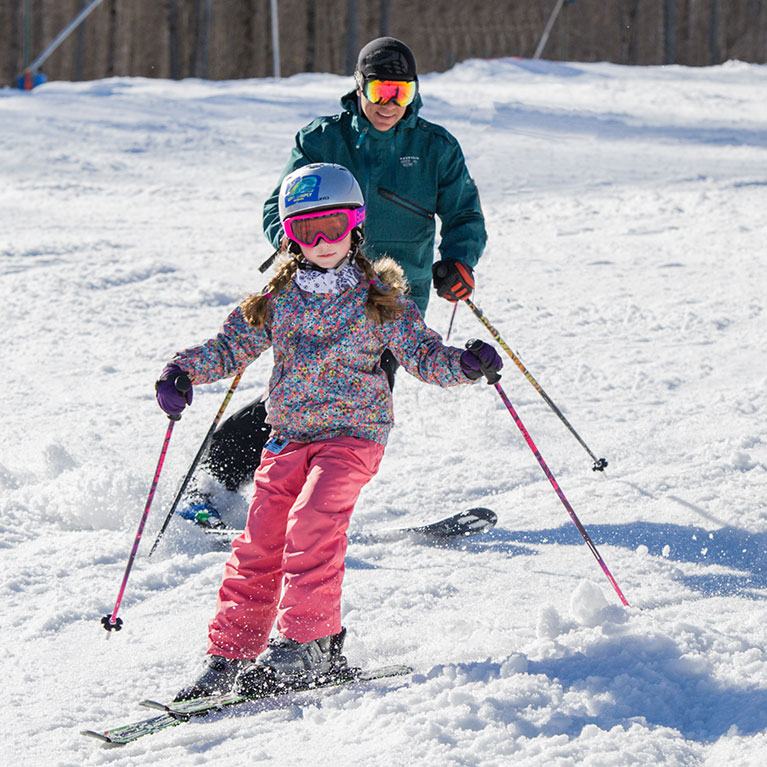 Girl skiing with dad